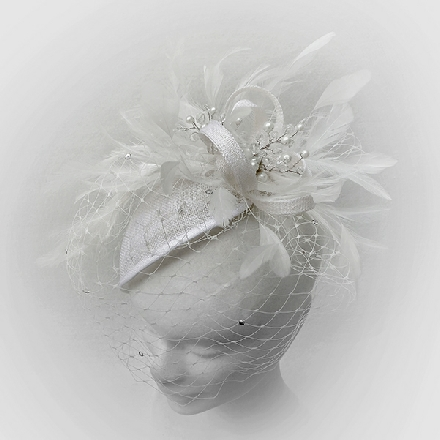 A feminine ivory teardrop fascinator with feathers, crystals, pearls and veil, perfect for brides, bridesmaids or wedding guests.