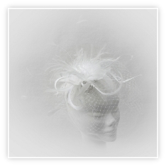 A feminine ivory white feather fascinator with crystals, pearls and veil, perfect for brides.